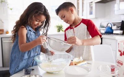 Brother and sister preparing cake mixture together at the kitchen table, waist up